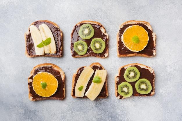 Sándwiches con pasta de chocolate y varias frutas en una mesa gris.