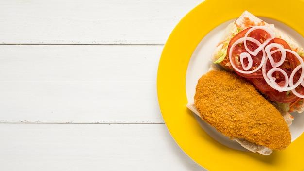 Sándwiches con pechuga de pollo y verduras frescas en placa.