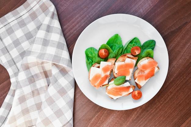 Sándwiches con pescado rojo en un plato blanco. decorado con verdes