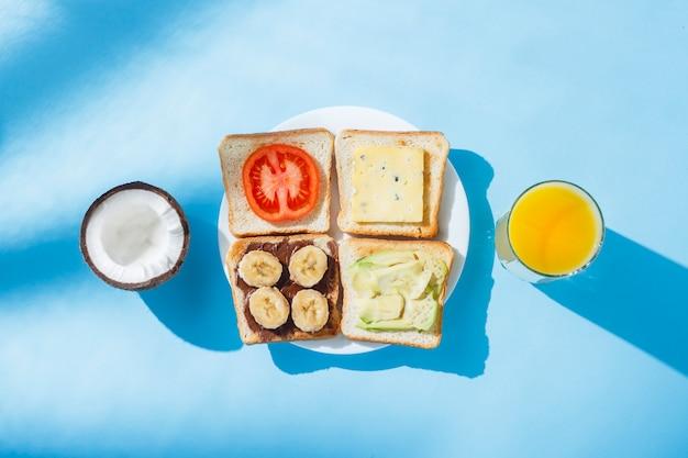 Sandwiches en un plato blanco, un vaso con jugo de naranja, coco, naranjas, superficie azul. vista plana, vista superior.