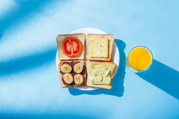 Sandwiches en un plato blanco, un vaso con jugo de naranja, una superficie azul. vista plana, vista superior.