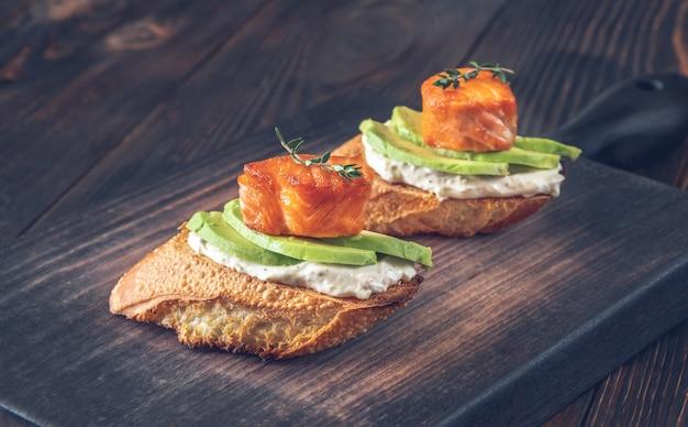 Sándwiches de queso crema, aguacate fresco y salmón frito