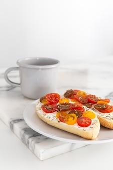 Sándwiches de queso crema y tomates con café