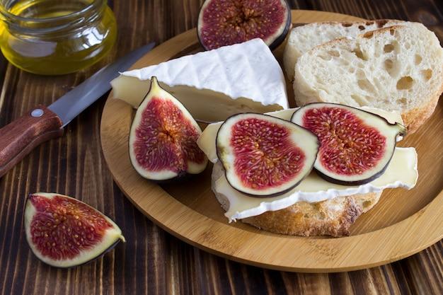 Sándwiches con queso e higos sobre tabla de cortar marrón