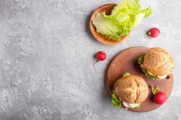Sándwiches con queso, rábano, lechuga y pepino sobre tabla de madera