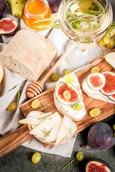 Sandwiches con queso ricotta o crema, ciabatta, higos frescos, peras, uvas, nueces y miel sobre tabla de madera sobre una mesa de piedra gris oscuro, con espacio de copia de copa de vino, vista superior