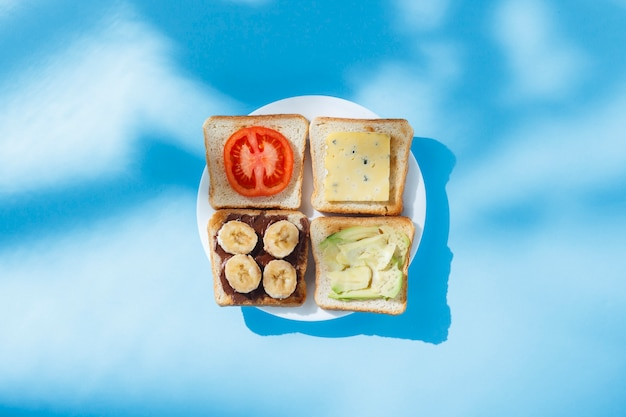 Sándwiches con queso, tomate, plátano y aguacate en un plato blanco, superficie azul. vista plana, vista superior.