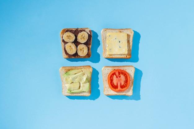 Sándwiches con queso, tomate, plátano y aguacate sobre una superficie azul. vista plana, vista superior.