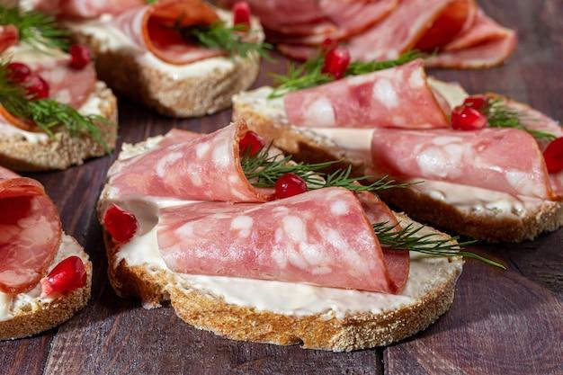 Sándwiches de salchicha ahumada y queso crema. decorado con hierbas de eneldo. sobre un fondo de madera oscura. copie el espacio.