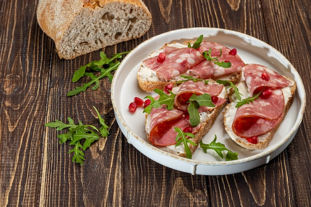 Sándwiches de salchicha ahumada y queso crema en un plato. decorado con hierbas de eneldo. sobre un fondo de madera oscura. copie el espacio.