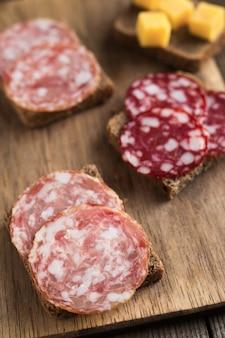 Sándwiches con salchichón ahumado y salchichas braunschweig de cerca sobre tabla de madera con cubitos de queso.