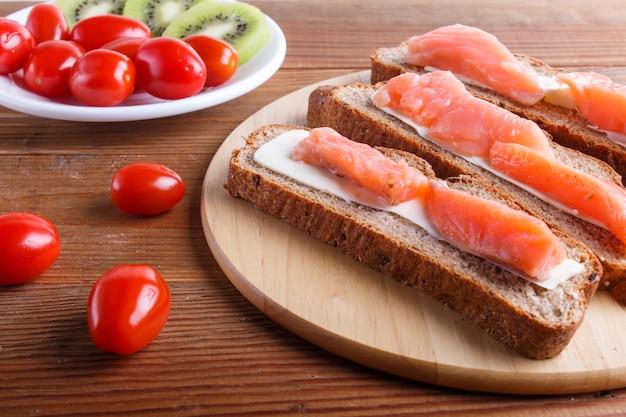 Sandwiches de salmón ahumado con mantequilla sobre fondo de madera