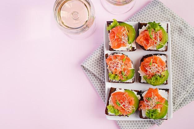 Sandwiches de salmón con queso crema y microverde. canapé con salmón. vista superior. lay flat