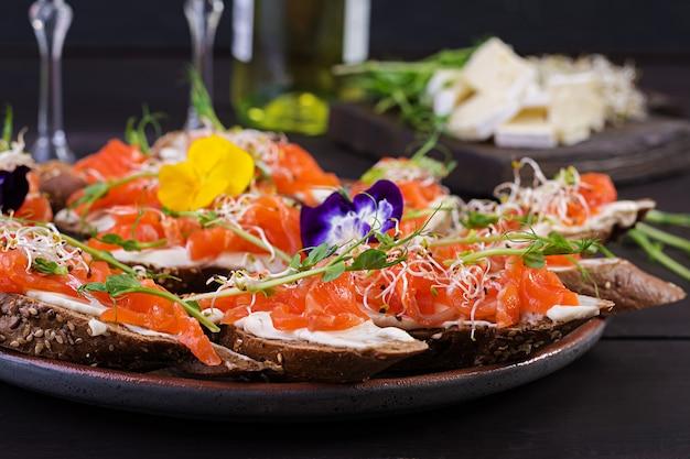 Sandwiches de salmón con queso crema y microverde en mesa de madera