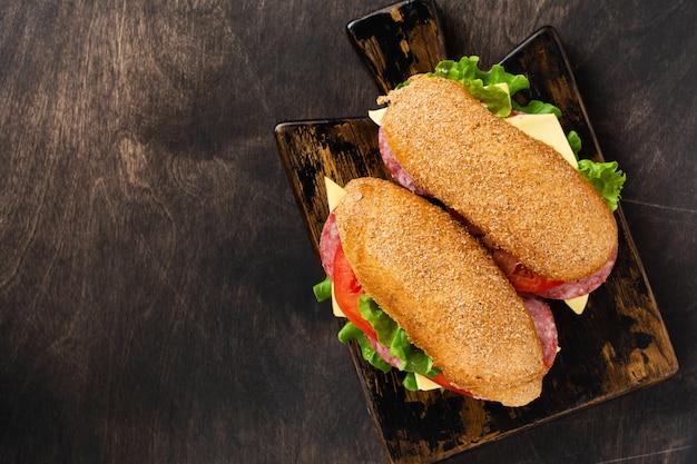 Sándwiches saludables con verduras y salami en rodajas sobre un soporte de madera rústica