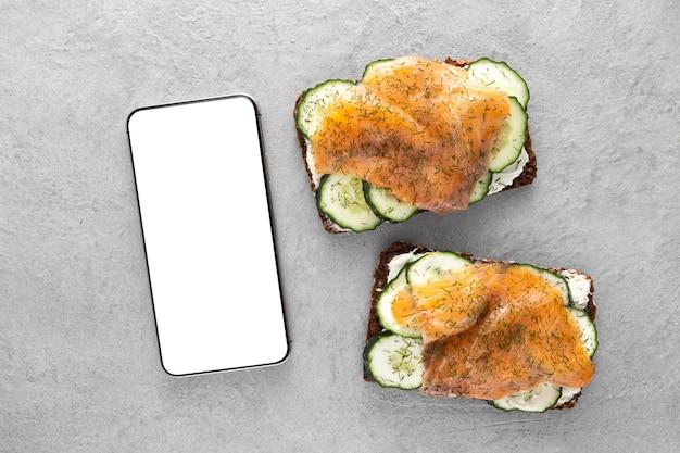 Sándwiches de vista superior con pepinos y salmón con teléfono en blanco