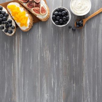 Sándwiches de vista superior con queso crema y frutas con espacio de copia
