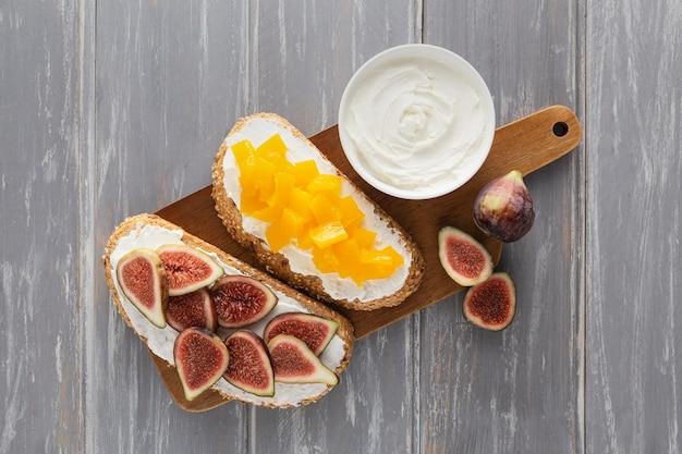 Sándwiches de vista superior con queso crema y frutas en la tabla de cortar
