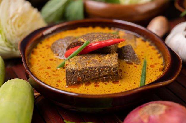 Sangre de pollo al curry en un bol con ají, cebolletas, pepino y cebolla morada