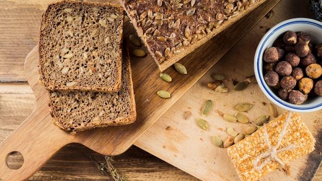 Sano pan de semillas de girasol y tazón de avellanas con barra de proteína en una tabla de cortar