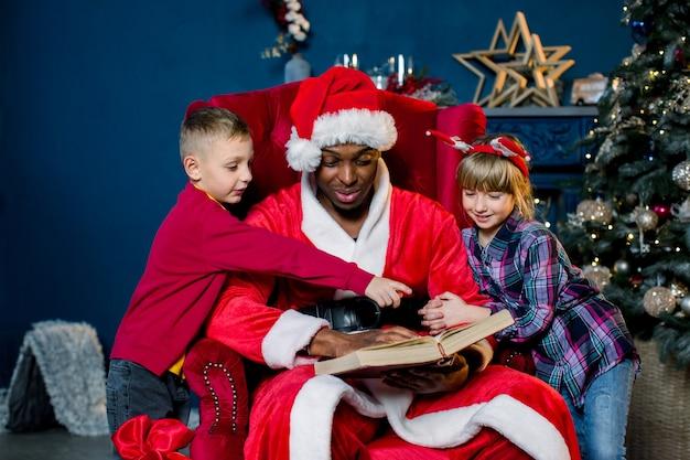 Santa claus africano leyendo un libro con historias de navidad para dos niños pequeños