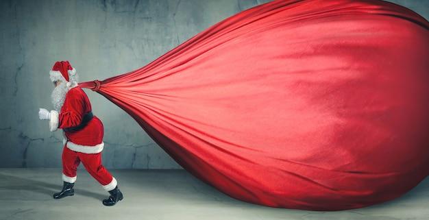 Santa claus con big bag en banner publicitario en blanco con espacio de copia. rebajas, tema navideño - imagen