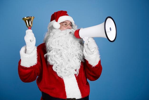 Santa claus con campanilla gritando por megáfono