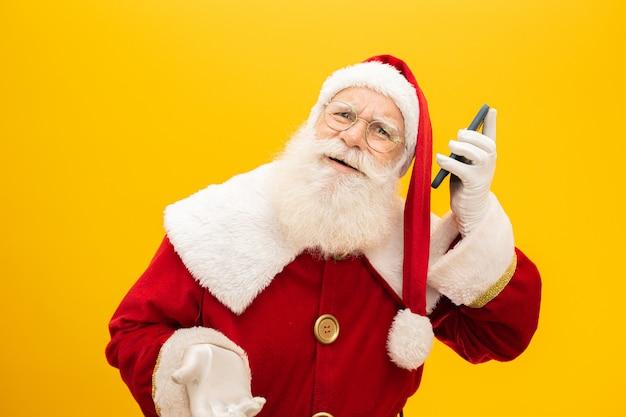 Santa claus con celular sobre fondo amarillo