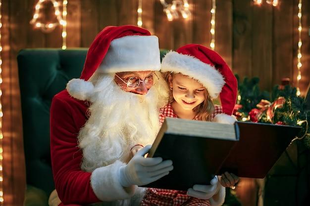 Santa claus dando un regalo a una niña linda