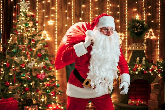 Santa claus con un gran saco de regalos en su habitación en casa cerca del árbol de navidad