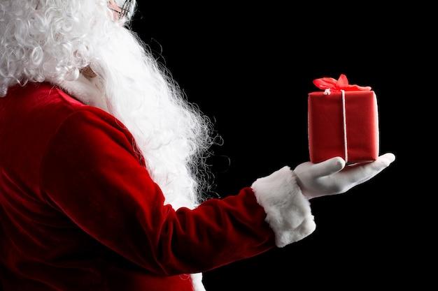 Santa claus con guantes manos sosteniendo con caja de regalo