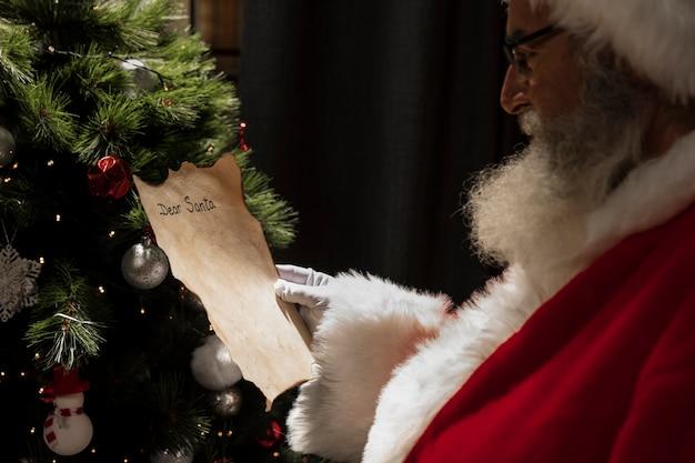 Santa claus leyendo una carta de navidad