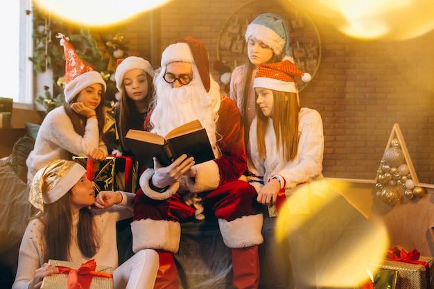Santa claus leyendo un libro a un grupo de niños