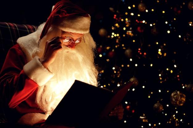 Santa claus leyendo un libro mágico mientras está sentado en una habitación oscura
