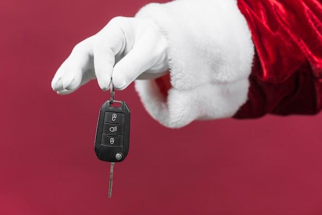 Santa claus mano sosteniendo la llave del coche