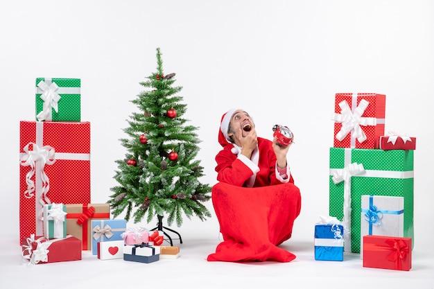 Santa claus mirando arriba sentado en el suelo y mostrando el reloj cerca de regalos y árbol de navidad decorado