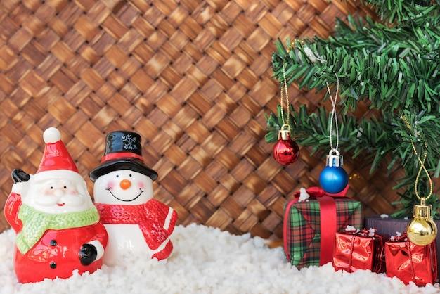 Santa claus y muñeco de nieve en el fondo de mimbre
