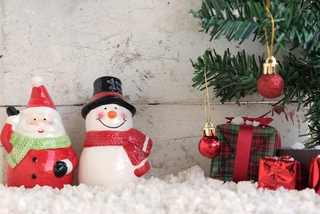 Santa claus y muñeco de nieve en la nieve con el árbol de navidad en el fondo de la vendimia
