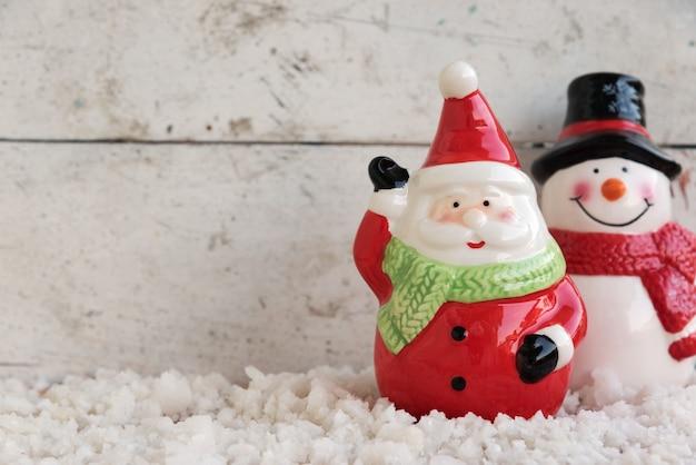 Santa claus y muñeco de nieve en la nieve