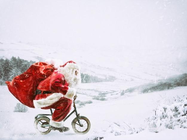 Santa claus en una pequeña bicicleta en un paisaje invernal bajo la nieve.