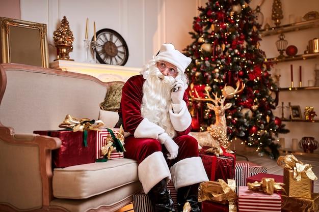 Santa claus sentado en el sofá y hablando por teléfono móvil cerca de la chimenea y el árbol de navidad con regalos. año nuevo y feliz navidad, felices fiestas concepto