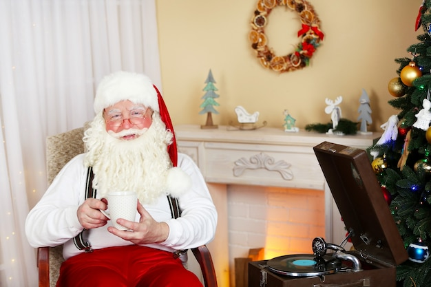 Santa claus sentado con una taza de bebida caliente en una silla cómoda junto a la chimenea en casa