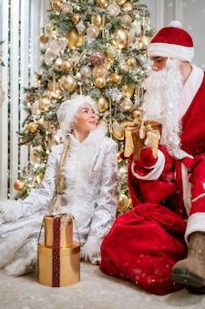 Santa claus y snegurochka posando junto al árbol de año nuevo