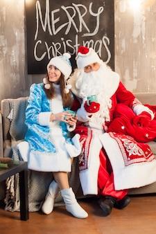 Santa claus y snow maiden están sentadas en el sofá y bebiendo té