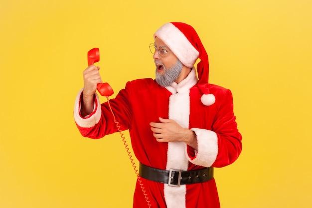 Santa claus sosteniendo un auricular retro, mirando el teléfono fijo con la boca abierta.