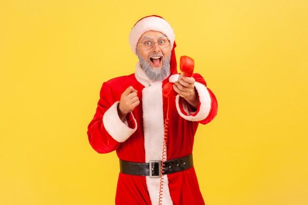 Santa claus sosteniendo el auricular del teléfono fijo, llamándolo para felicitarlo con festivales