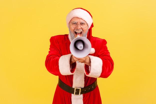 Santa claus sosteniendo el megáfono en las manos y haciendo un anuncio en voz alta, mirando a la cámara.