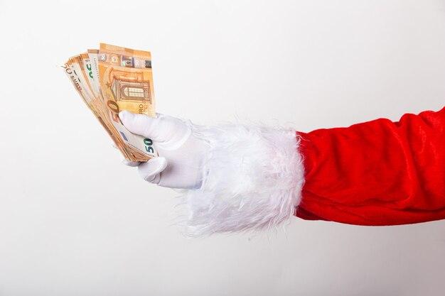 Santa claus tiene dinero sobre fondo blanco.