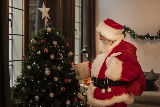 Santa claus tocando el árbol de navidad