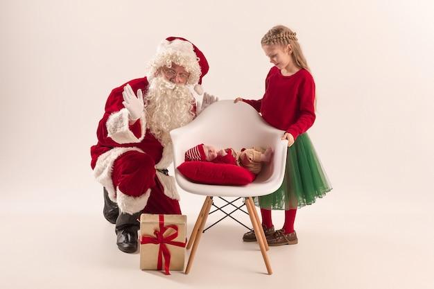 Santa claus en traje rojo con una niña y un bebé aislado en blanco